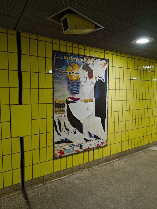 Yellow tiled wall and cctv in a subway tunnel, Hamburg